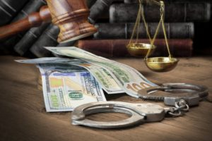 Money, gavel, and handcuffs on the table