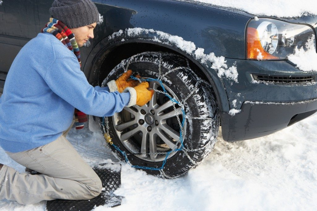 Man Putting Snow Chains Onto Tire Of Car
