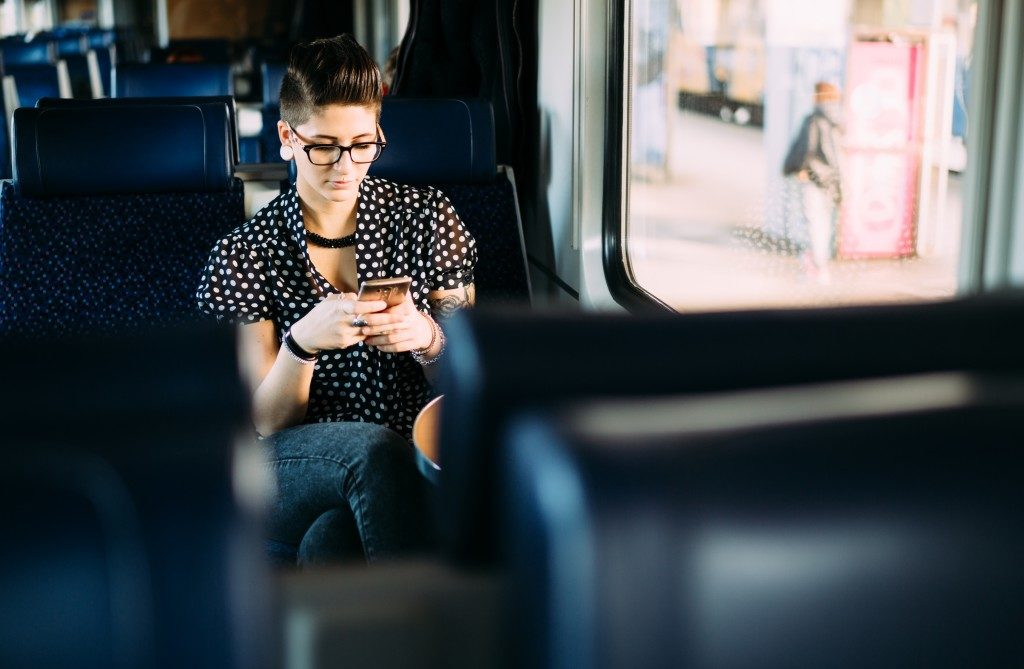 Millenial young woman texting on train